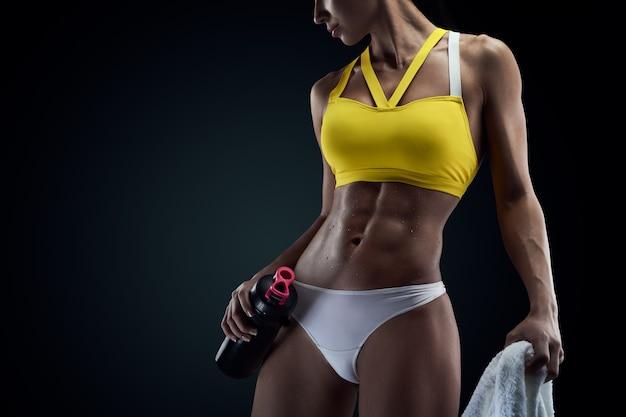 Copyspace와 검은 배경에 여성 운동 선수의 완벽한 복부 근육의 수평 스튜디오 샷