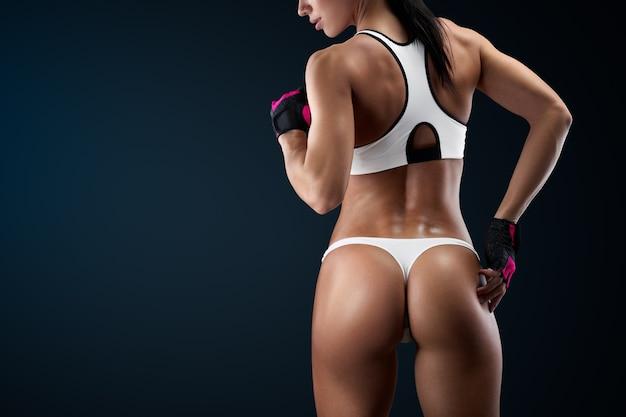 검정색 배경에 복사 공간이 있는 수평 스튜디오 샷. 그녀의 잘 단련된 몸을 보여주는 체육관에서 휴식을 취하는 땀에 젖은 여자.