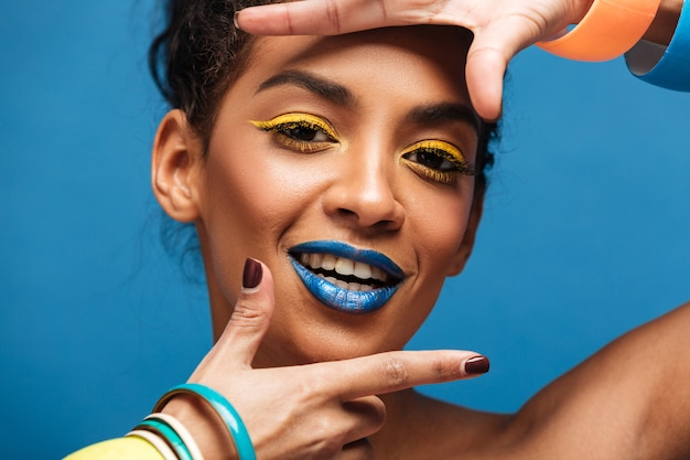 Horizontal stylish mulatto woman with colorful makeup and curly hair in bun gesturing on camera with smile isolated, over blue wall