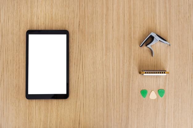 Горизонтальный вид сверху экрана смартфона с пустым содержимым. изучите и изучите уроки игры на гитаре онлайн понятие. исследуйте музыку и технологии вместе. гитарные кирки, гармоника и гитарный мост.