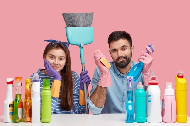Horizontal view of attractive woman with dark hair, wears headband and protective gloves, sit closely to each other, surronded with cleaning agent