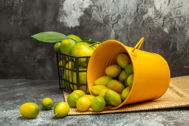 Vista orizzontale del cesto nero con mandarini verdi freschi e secchio caduto con kumquat su giornali su tavola grigia