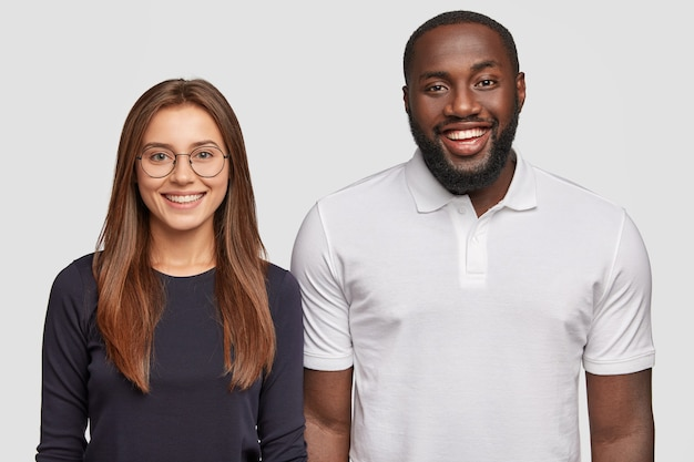 Horizontal view of cheerful dark skinned young man and european woman have positive expressions