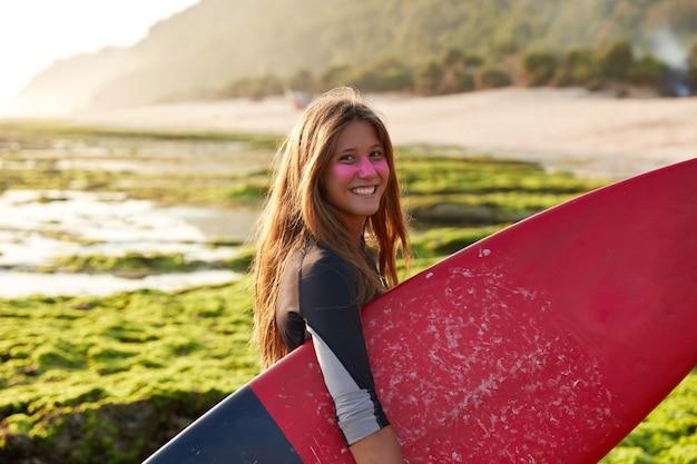 Horizontal view of cheerful european surfer surfes being in high spirit, carries board