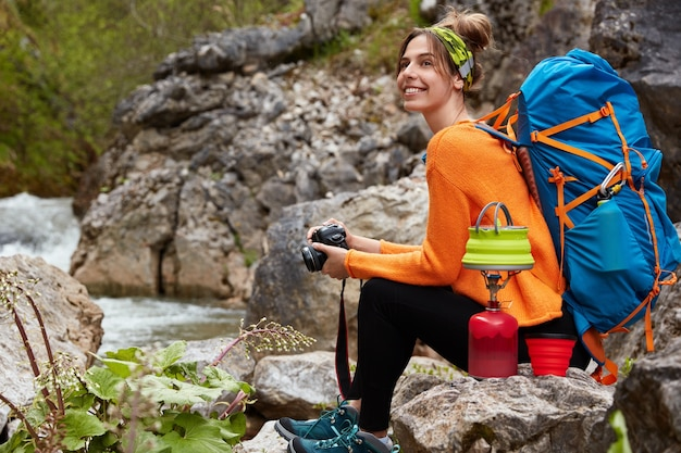 Horizontal view of cheerful pleased woman sits near rock pool, holds modern camera, prepares hot drink, enjoys camping and traveling, wears active wear