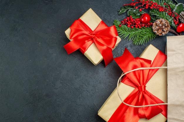 Vista orizzontale dell'atmosfera natalizia con bellissimi doni e cono di conifere rami di abete su sfondo scuro