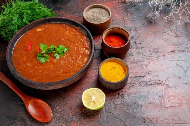 Vista orizzontale della classica zuppa di pomodoro in una ciotola marrone e diverse spezie sulla tavola di colori misti