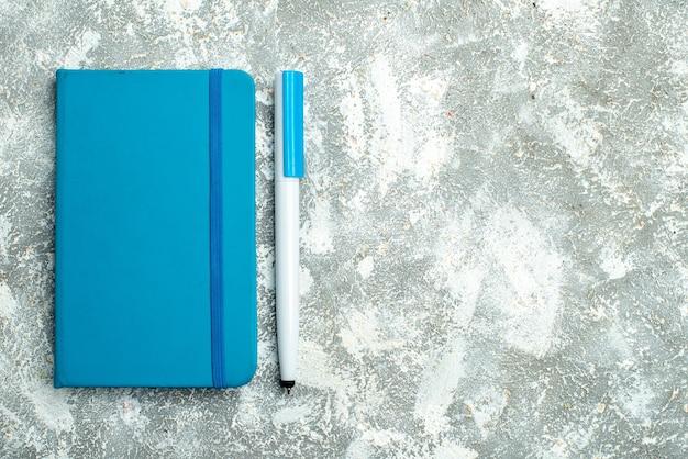 Vista orizzontale del taccuino blu chiuso e della penna sdraiati su sfondo bianco