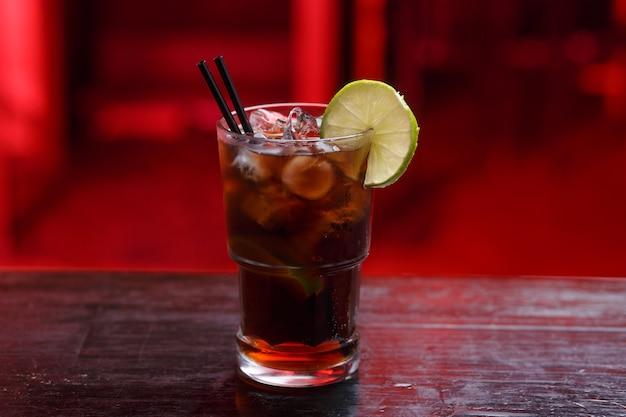 Горизонтальный вид. крупный план коктейля cuba libre в длинном стакане, джин, стоя на барной стойке, изолированном на красном пространстве.