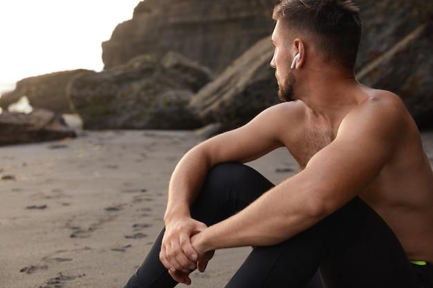 La vista orizzontale dello sportivo contemplativo si siede sulla sabbia, messa a fuoco da parte in lontananza