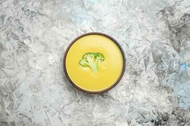 Vista orizzontale della crema di zuppa di broccoli in una ciotola marrone sul tavolo bianco