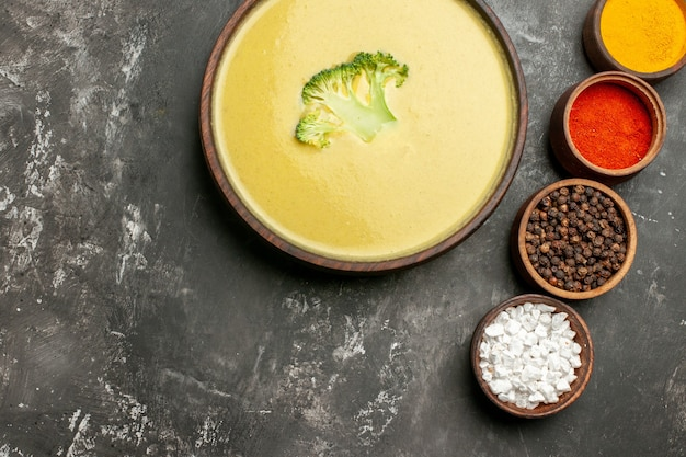 Horizontal view of creamy broccoli soup in a brown bowl and different spices on gray table