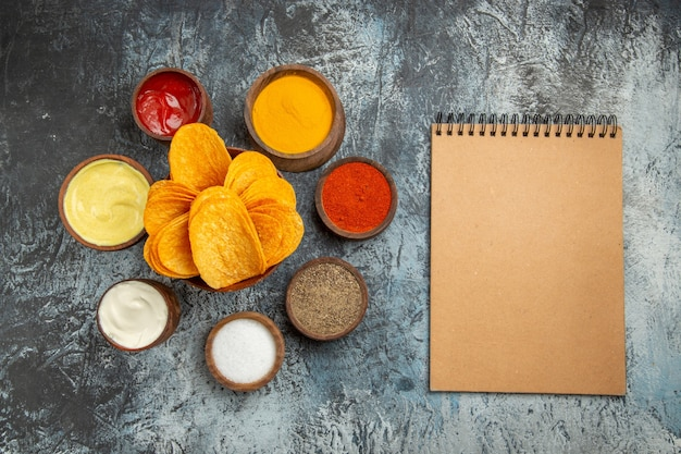 Horizontal view of crispy chips on wooden cutting board served with different spices mayonnaise ketchup and notebook on gray table