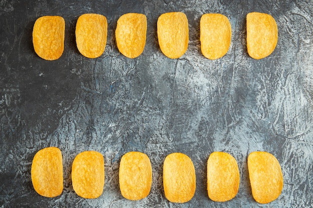 Vista orizzontale del croccante al forno cinque patatine allineate sul tavolo grigio stock photo