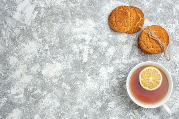 Vista orizzontale di una tazza di tè nero con limone e biscotti deliziosi sulla superficie del ghiaccio