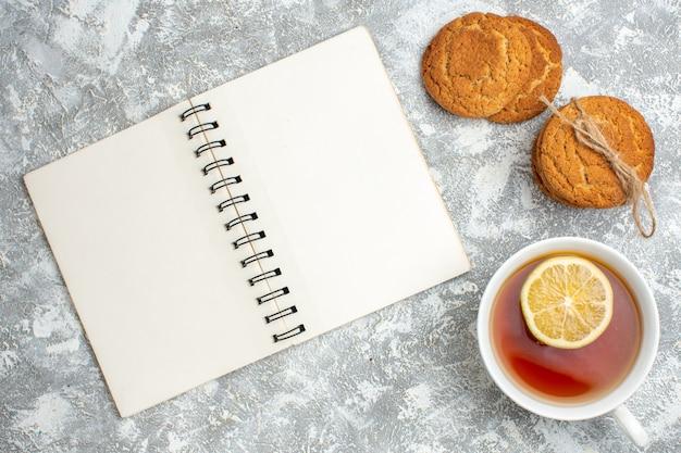 Vista orizzontale di una tazza di tè nero con limone e biscotti deliziosi e taccuino aperto sulla superficie del ghiaccio
