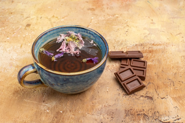 Horizontal view of a cup of hot herbal tea and chocolate bars on mixed color table