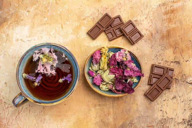 Horizontal view of a cup of hot herbal tea flowers and chocolate bars on mixed color table