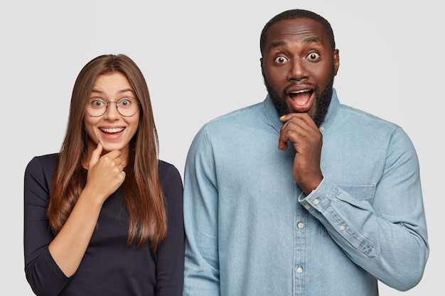 Horizontal view of curious emotional surprised diverse girlfriend and boyfriend keeps jaw dropped from amazement