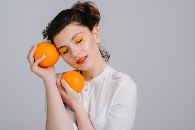Horizontal view of the cute caucasian woman with closed eyes holding citrus fruits and posing to the camera. people emotions concept