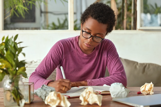 Horizontal view of dark skinned woman plans working process, notetats information in notepad, writes down text, poses at cozy interior with papers. female blogger makes notes for publication