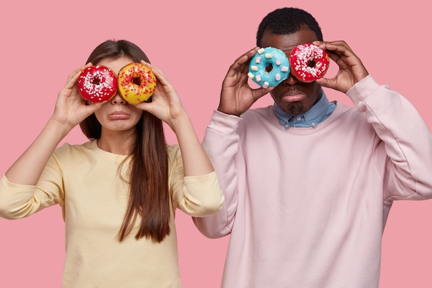 Horizontal view of dejected mixed race lady and guy cover eyes with delicious, dressed jumpers, going to have sweet snack