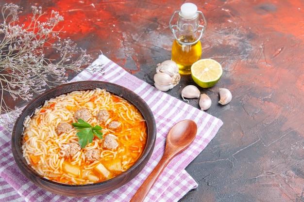 Vista orizzontale di deliziosa zuppa di pollo con noodles verdi e cucchiaio su asciugamano rosa spogliato bottiglia di olio aglio limone su sfondo scuro