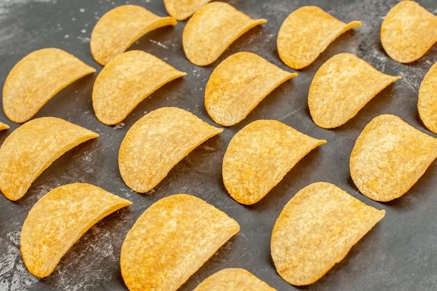 Vista orizzontale di deliziose patatine fatte in casa posate sul tavolo grigio