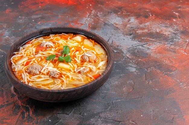 Vista orizzontale di una deliziosa zuppa di noodle con pollo in una ciotola marrone sullo sfondo scuro