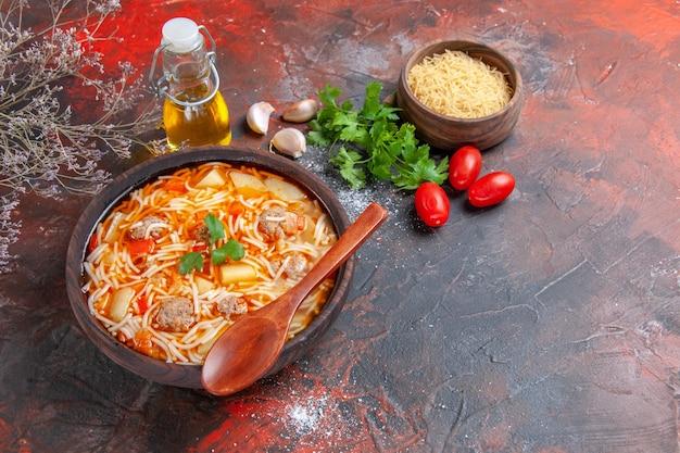 Vista orizzontale di deliziosa zuppa di noodle con pollo e pasta cruda in una piccola ciotola marrone e cucchiaio di pomodori e verdure all'aglio sullo sfondo scuro