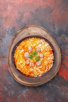 Vista orizzontale di deliziosa zuppa di noodle con pollo su tagliere di legno su sfondo scuro