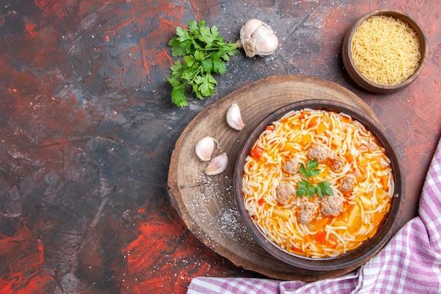 Vista orizzontale di una deliziosa zuppa di noodle con pollo su tagliere di legno verdi cucchiaio di aglio su sfondo scuro