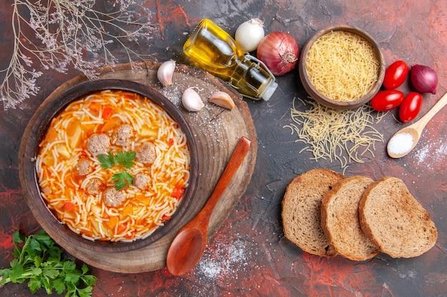 Vista orizzontale di una deliziosa zuppa di noodle con pollo su tagliere di legno verdure cucchiaio aglio pomodoro e fette di pane su sfondo scuro