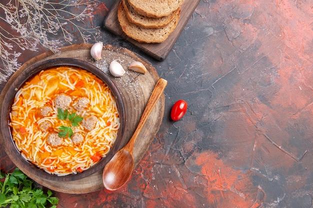 Vista orizzontale di una deliziosa zuppa di noodle con pollo su tagliere di legno verdi cucchiaio aglio e pomodoro su sfondo scuro