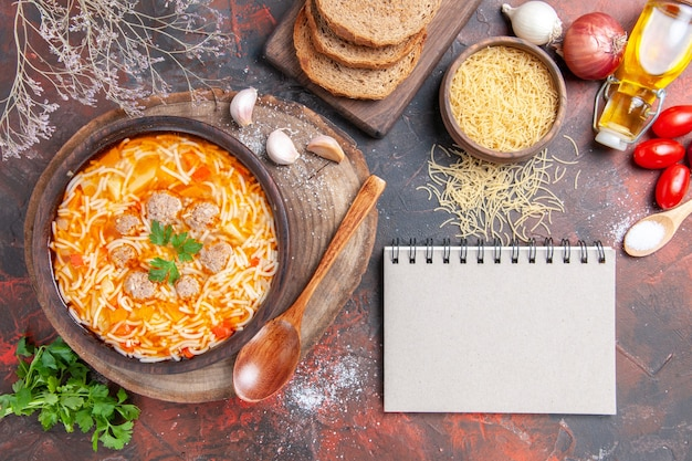 Horizontal view of delicious noodle soup with chicken on wooden cutting board greens spoon garlic tomato and notebook on dark background