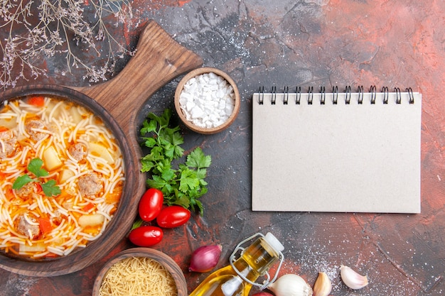 Horizontal view of delicious noodle soup with chicken on wooden cutting board salt onion uncooa bunch of greens tomatoes and notebook on dark background