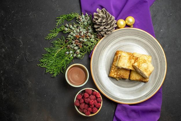 Vista orizzontale di deliziose frittelle su un piatto bianco di cioccolato e accessori per la decorazione di lamponi su un asciugamano viola su sfondo nero