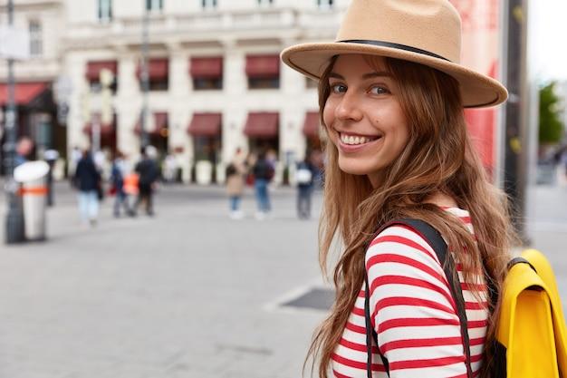 Vista orizzontale del turista femminile felice cammina sulla strada Foto Gratuite
