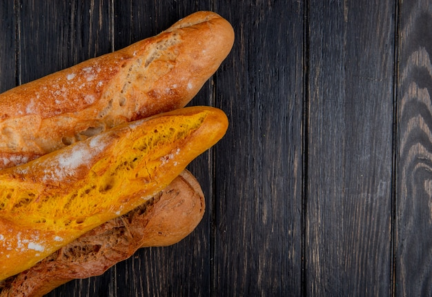 Horizontal view of different types of baguette on wooden background with copy space
