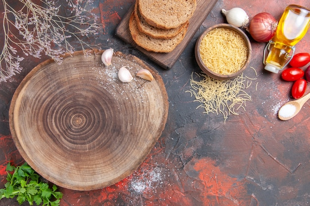 Horizontal view of dinner background wooden cutting board greens spoon garlic and tomato on dark background