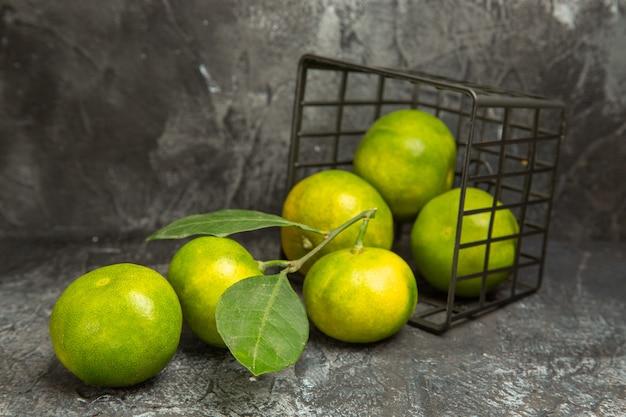 Vista orizzontale del cesto caduto con mandarini verdi freschi su sfondo grigio