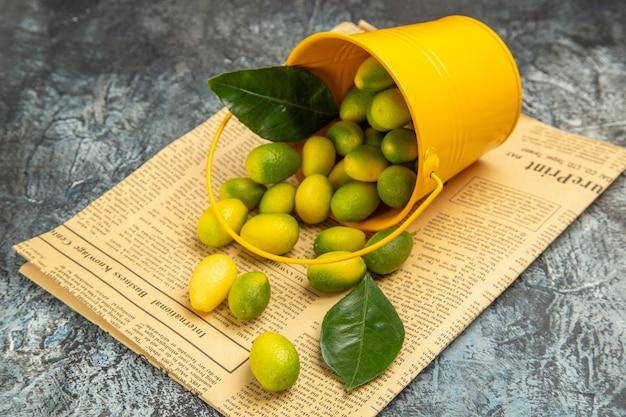 Vista orizzontale del secchio giallo caduto con kumquat freschi sui giornali sul tavolo grigio