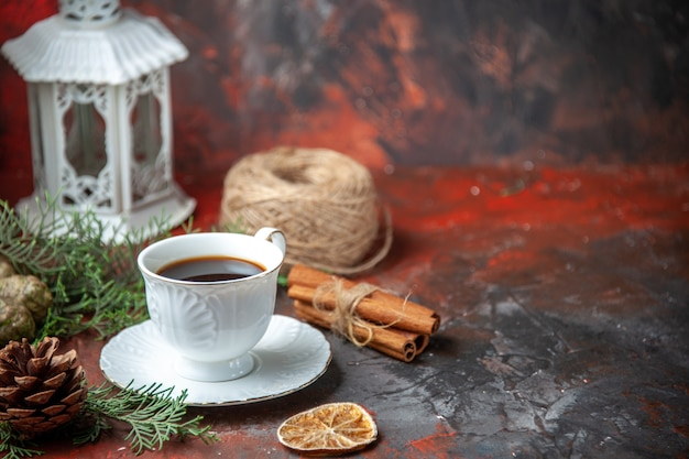 Vista orizzontale dei rami di abete lime cannella cono di conifere una palla di corda una tazza di tè nero su fondo rosso