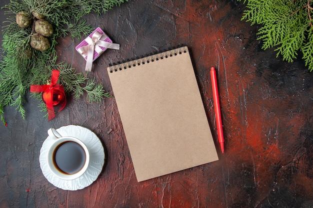 Vista orizzontale dei rami di abete una tazza di accessori per la decorazione del tè nero e un regalo accanto al taccuino con penna su sfondo scuro