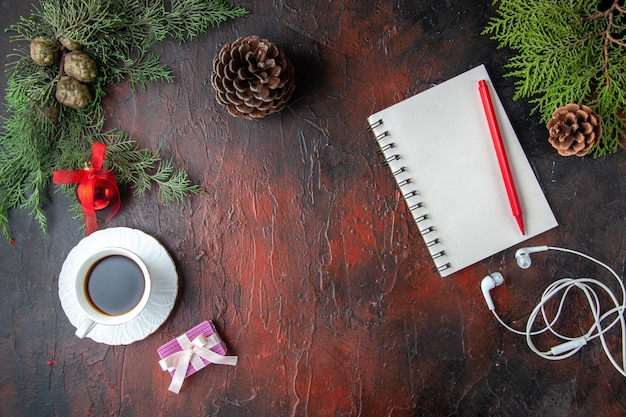 Horizontal view of fir branches a cup of black tea decoration accessories white headphone and gift next to notebook with pen on dark background