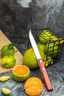 Vista orizzontale di agrumi freschi con foglie cadute da un cesto nero tagliato a metà e coltello su giornale su sfondo grigio
