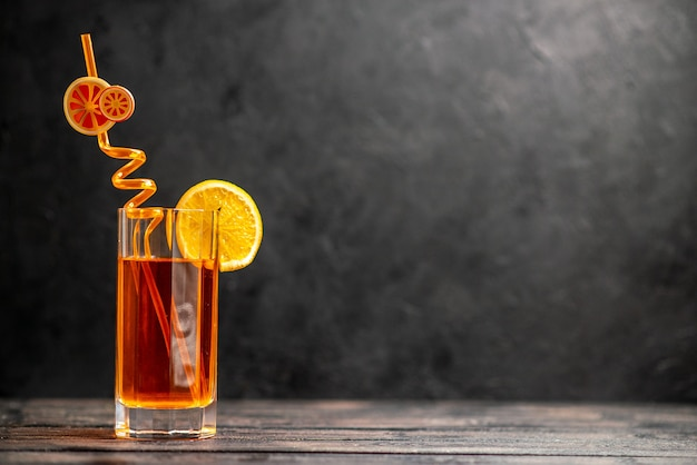 Horizontal view of fresh delicious juice in a glass with orange lime and tube on dark background