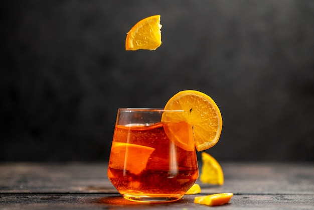 Horizontal view of fresh delicious juice in a glass with orange limes on dark background