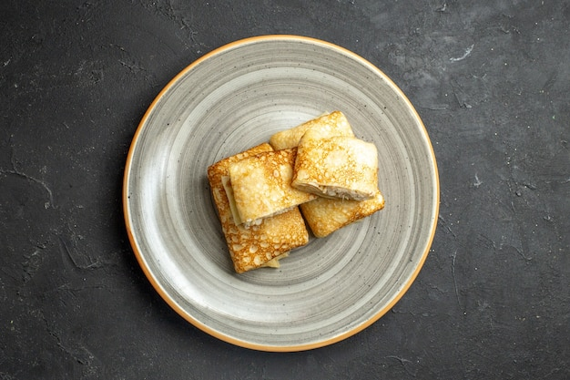 Vista orizzontale di frittelle orizzontali fresche su un piatto bianco su sfondo scuro