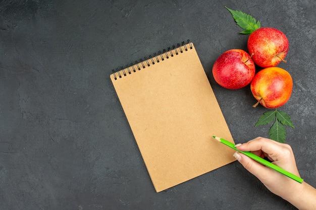 Vista orizzontale di mele rosse fresche con foglie e quaderno a spirale con penna su sfondo nero